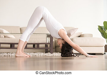 Young attractive woman in adho mukha svanasana pose, living...