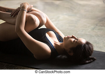 Young attractive woman in Apanasana pose, close up