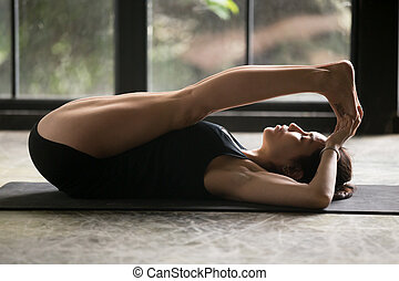 Young attractive woman in Apanasana pose, window background