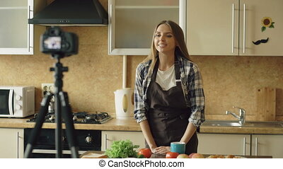 Young attractive woman in apron shooting video food blog about cooking on dslr camera in kitchen