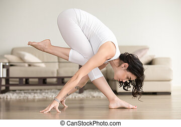 Young attractive woman in balance pose, at the living room