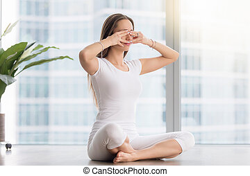 Young attractive woman in Bhramari Pranayama pose against...
