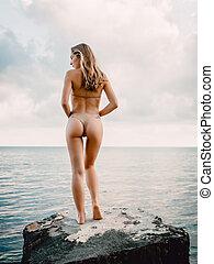 Young attractive woman in bikini posing at stones. Slim bikini girl at sea