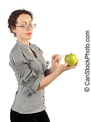 young attractive woman in business dress holding an apple and pointing on it for a pen isolated on white