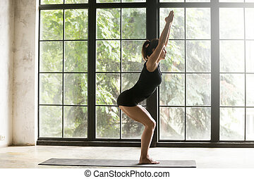 Young attractive woman in Chair pose, window background
