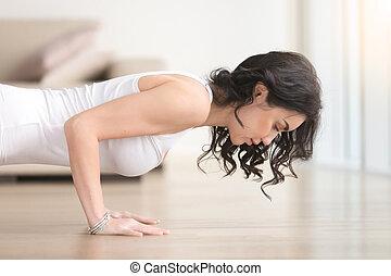 Young attractive woman in chaturanga dandasana pose, living...