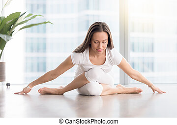 Young attractive woman in Gomukasana pose against floor window