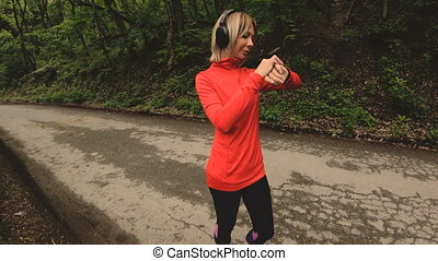 Young attractive woman in headphones changing the settings...