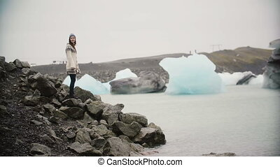 Young attractive woman in lopapeysa standing in ice lagoon. Tourist exploring the famous sight of Iceland alone.