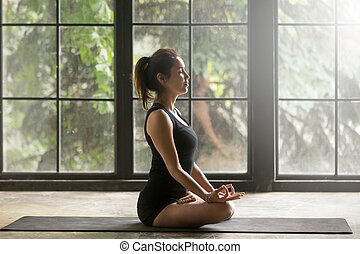 Young attractive woman in Lotus pose, window background