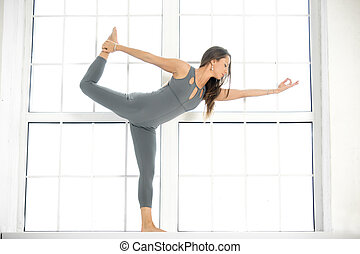 Young attractive woman in Natarajasana pose, window background