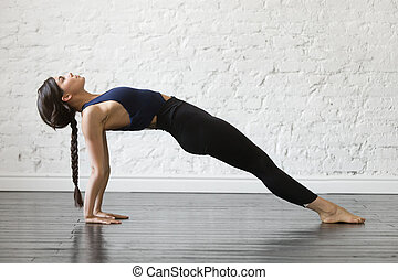 Young attractive woman in Purvottanasana pose, studio background