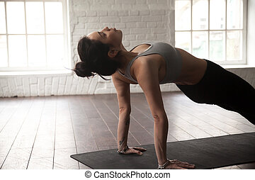 Young attractive woman in Purvottanasana pose, white loft studio