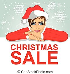 young attractive woman in santa hat leaned on blank board with red christmas sale text