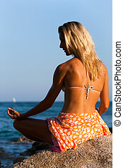 Young attractive woman in spiritual yoga position outdoors.