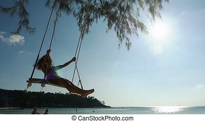 Young attractive woman in sunglasses and bikini is swinging on the swing at tropical beach with shining lens lare effects. slow motion. 1920x1080