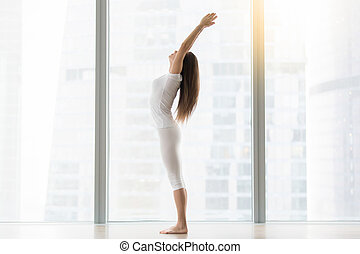 Young attractive woman in Tadasana pose against floor window...