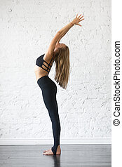 Young attractive woman in Tadasana pose, studio background