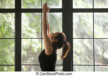 Young attractive woman in Tadasana pose, window background