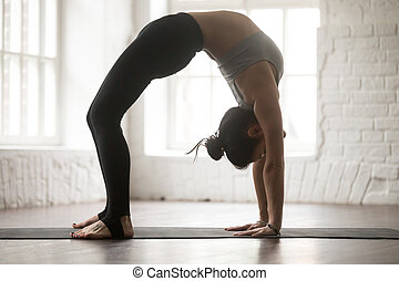Young attractive woman in Urdhva Dhanurasana pose, white loft st