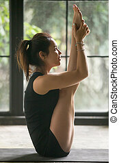 Young attractive woman in urdhva mukha paschimottanasana pose, s
