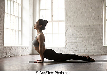 Young attractive woman in Urdhva mukha shvanasana pose, loft stu