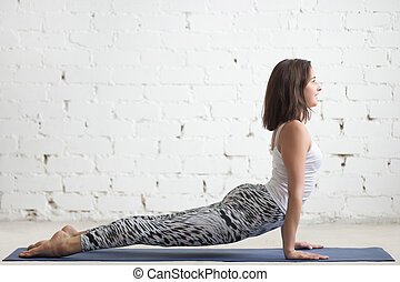 Young attractive woman in Urdhva mukha shvanasana pose, white st