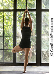 Young attractive woman in Vrksasana pose, window background