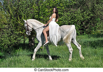 young attractive woman in white dress horseback riding