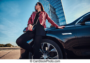 Young attractive woman is chilling in bright sunny day next to her car