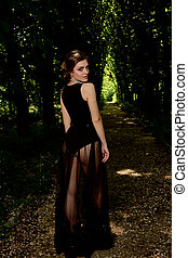 Young attractive woman is wearing the sexy transparent black dress. Young woman modern portrait.