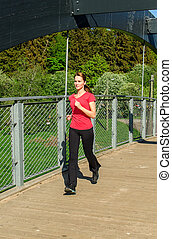 Young attractive woman jogging on the bridge