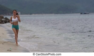 Young attractive woman jogging on the beach and use smartphone