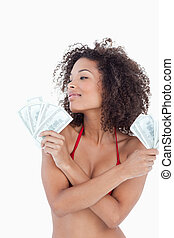 Young attractive woman looking away while holding bank notes