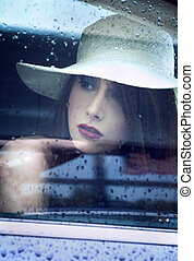 Young attractive woman looking through window after rain