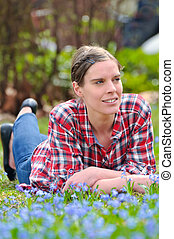 Young attractive woman lying on a meadow with blossoming blue Scilla bifolia in spring and is enjoying the warm sunlight