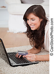 Young attractive woman making a payment with a credit card on the internet while lying on a carpet in the living room