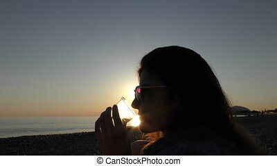 Young attractive woman on the beach at sunset drinking from...