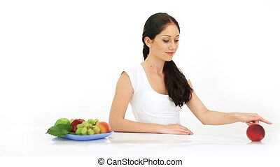 Young attractive woman playing with red peach fruit