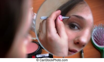 Young attractive woman plucking her eyebrows with tweezers before a mirror. Powder her cheeks and smiling