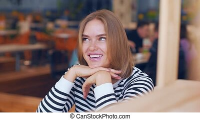 Young attractive woman posing in cafe.