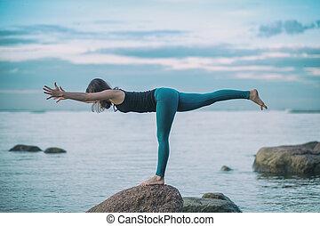 Young attractive woman practicing yoga, standing in Warrior three exercise, Virabhadrasana III pose
