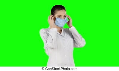 Young attractive woman putting on health mask. Green screen