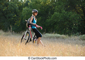 Young Attractive Woman Resting with Bike on the Beautiful Meadow in the Forest