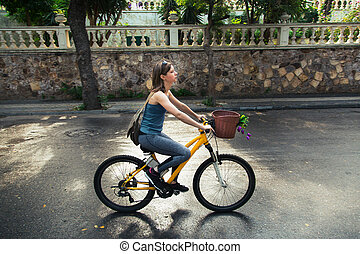 Young attractive woman riding a bicycle.