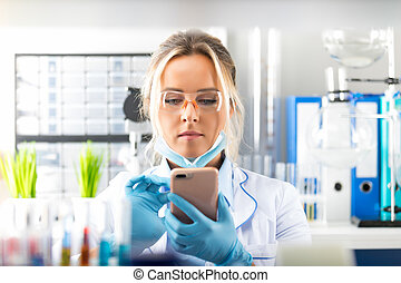 Young attractive woman scientist using smartphone in the laboratory