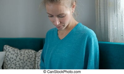 Young attractive woman sits at home on the sofa using desktop tablet.