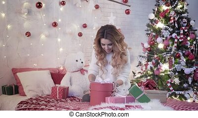 Young attractive woman sits on a bed near the Christmas tree and unpacks presents