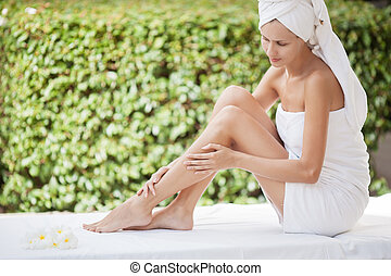 Young attractive woman sitting on a massage table