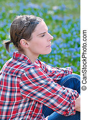 Young attractive woman sitting on a meadow with Scilla bifolia in spring